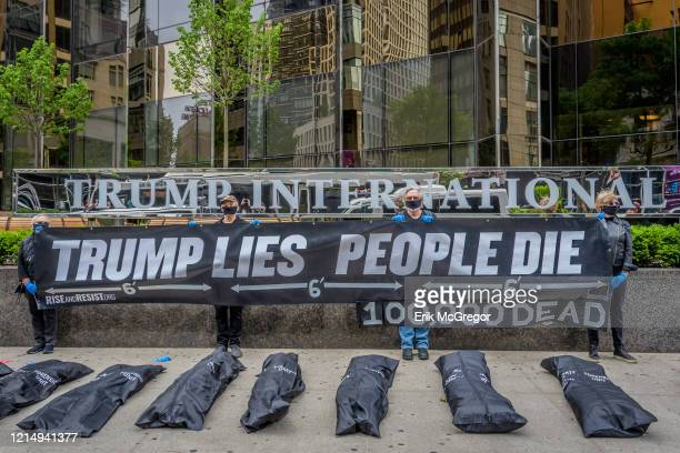 Activists placed body bags outside Trump International Hotel and Tower while other protesters held a banner that read: TRUMP LIES, PEOPLE DIE and...