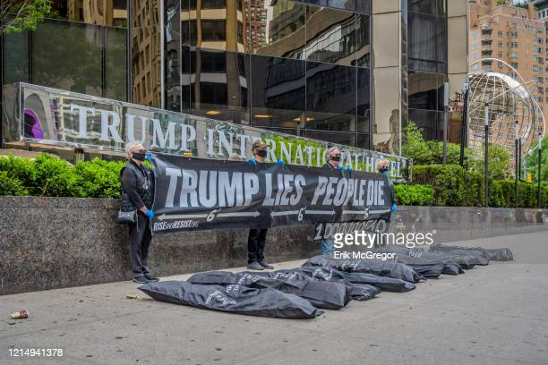 Activists placed body bags outside Trump International Hotel and Tower while other protesters held a banner that read TRUMP LIES PEOPLE DIE and...
