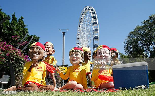 Activists pose for pictures with heads depicting some of the G20 leaders during a protests against inequality on November 14 2014 in Brisbane...