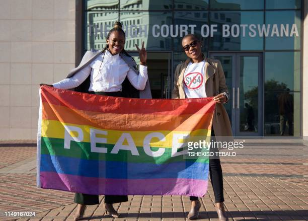TOPSHOT Activists pose with a rainbow flag as they celebrate outside Botswana High Court in Gaborone on June 11 2019 Botswana's Court ruled on June...