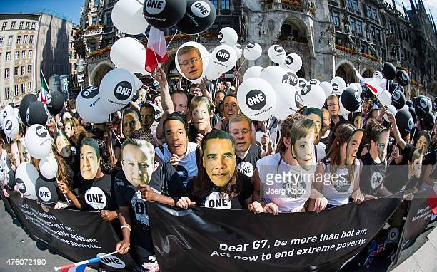 Activists pose with masks of the leaders of the G7 nations during a demonstration by international campaigning and advocacy organization 'ONE' ahead...