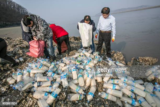 Activists pour down PET bottles on an island before throwing them to the water near the DMZ on January 17 2018 in Incheon South Korea The human...