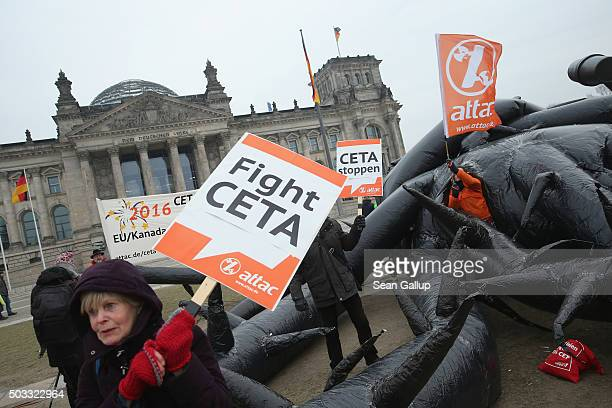 Activists pretend to battle an inflatable monster meant to represent the CETA trade agreement outside the Reichstag on January 4 2016 in Berlin...