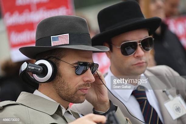 Activists pretending to be secret agents from the US National Security Agency and the German federal intelligence service join colleagues protesting...
