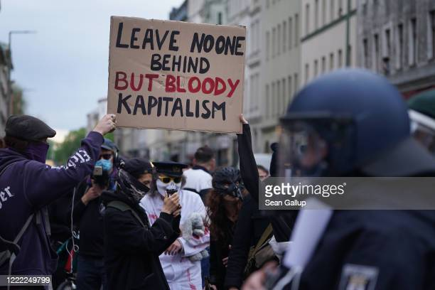 Activists protest against capitalism as riot police stand nearby during scattered leftwing protests in Kreuzberg district on May Day during the novel...