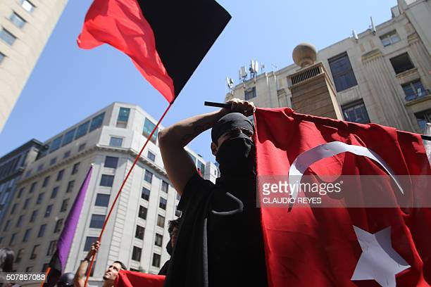 Activists protest against the visit of Turkish President Recep Tayyip Erdogan in front of La Moneda Presidential Palace in Santiago on February 1...