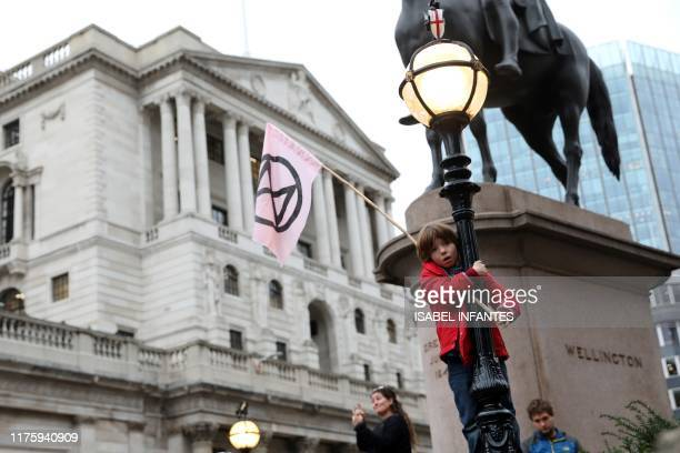 Activists protest outside of the Bank of England during the eighth day of demonstrations by the climate change action group Extinction Rebellion in...