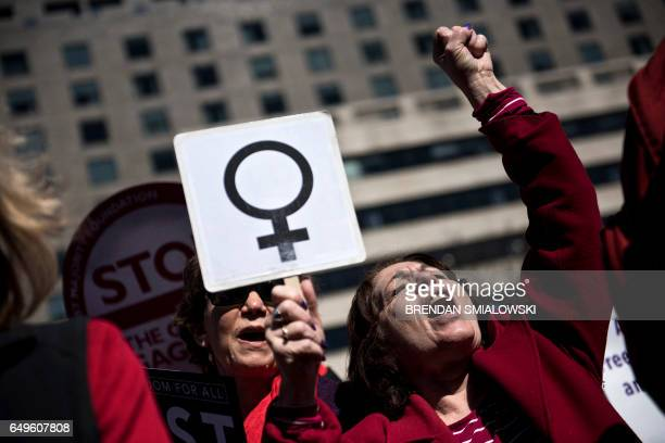 TOPSHOT Activists protest the Trump administration and rally for women's rights during a march to honor International Woman's Day on March 8 2017 in...