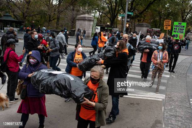 Activists protest using body bags for Trump administration moves as overturn the election, his Covid Program and whipping up MAGA fascist mobs and...