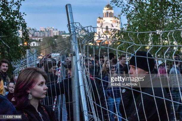 Activists protesting against a plan to build an Orthodox cathedral gather around a fenced off construction site in a park in the Russian Urals city...
