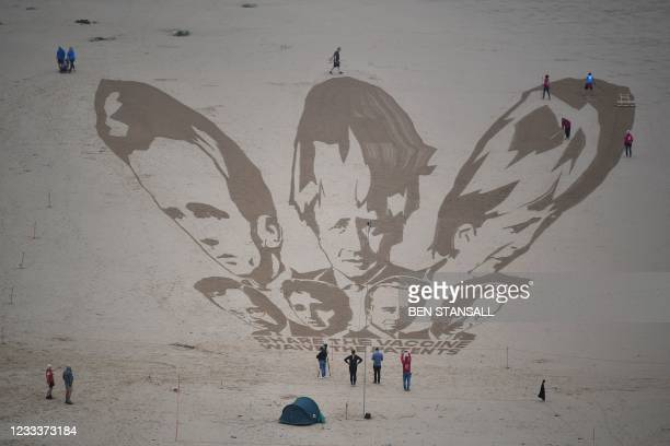Activists put the finishing touches to a sand drawing of the G7 leaders and calling on them to 'share the vaccine and waive the patents' on Watergate...
