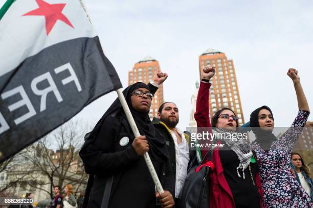Activists raise their fists during a 'Women For Syria' vigil at Union Square, April 13, 2017 in New York City. The group gathered to support and...