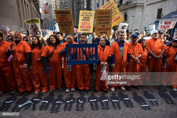 Activists rally against financial institutions' support of private prisons and immigrant detention centers as part of a May Day protest near Wall...