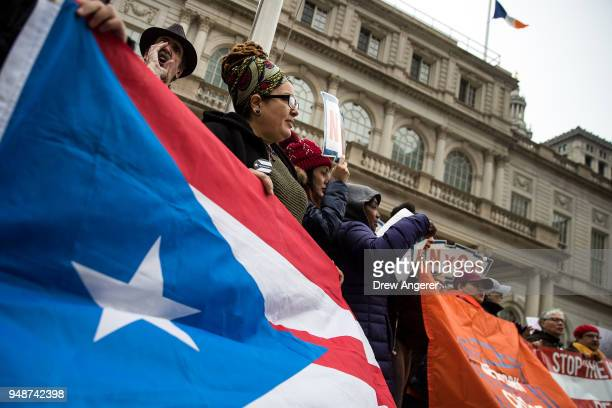 Activists rally in support of Puerto Rican families displaced by Hurricane Maria on the steps of City Hall April 19 2018 in New York City Many Puerto...