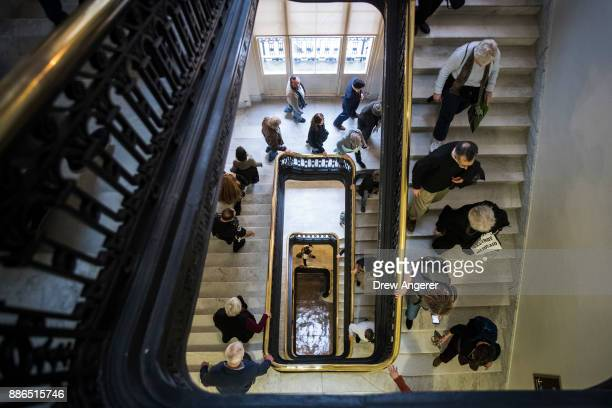 Activists rallying against the GOP tax reform bill make their way through the Cannon House Office building on Capitol Hill December 5 2017 in...