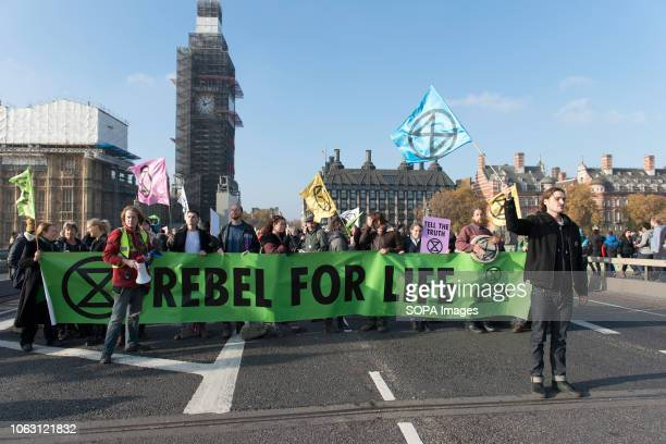 Activists seen carrying a banner and flags with the Extinction Rebellion logo stamped on it Extinction Rebellion activists gathered at five main...