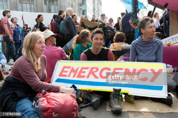 Activists seen holding a placard during the Extinction Rebellion Strike in London Environmental activists from Extinction Rebellion movement hold for...