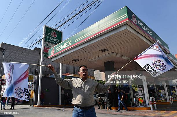 Activists shout slogans against the rise in fuel prices while blocking a gas station along Tlalpan avenue during a protest in Mexico City on January...