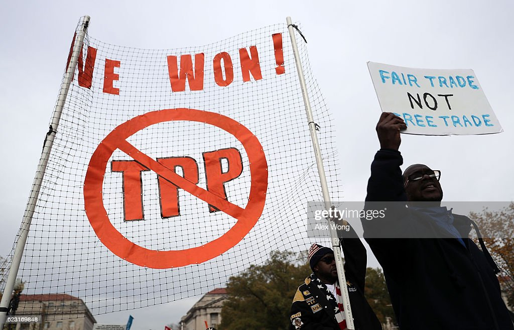 Activists shout slogans as they march during an anti-Trump and anti-TPP protest November 14, 2016 in Washington, DC. Activists held a rally and a march 'to protest the Trans-Pacific Partnership and urge President-elect Donald Trump and members of Congress to reject the trade deal.'