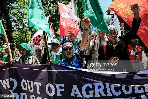 Activists shout slogans during a protest against the World Trade Organization meeting on December 3 2013 in Denpasar Indonesia Thousands of farmers...