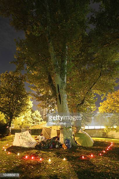 Activists sit around tents among some of the nearly 300 trees slated for removal in the Schlosspark next to Hauptbahnhof train station on October 6...