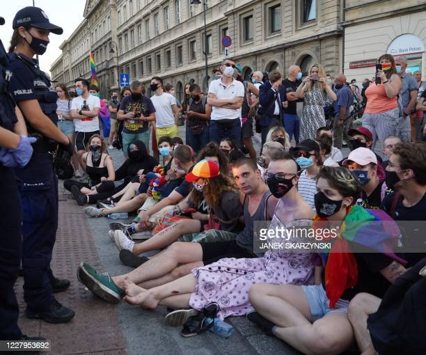 Activists sit to block a police vehicle transporting detained gay-right activist Margo in Warsaw, Poland, on August 7,2020. - Polish police arrested...