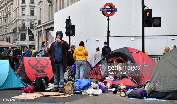 Activists sit with thier tents in the road after sleeping at Oxford Circus on the second day of an environmental protest by the Extinction Rebellion...