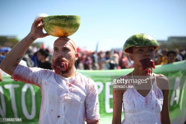 TOPSHOT Activists some carrying watermelons on their heads in alution to Brazil's Congress building demonstrate during a protest against Brazil's...