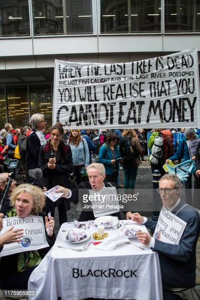 Activists stage a mock dinner and eat fake money outside the offices of Blackrock asset managers during a protest in the City of London on 14th...