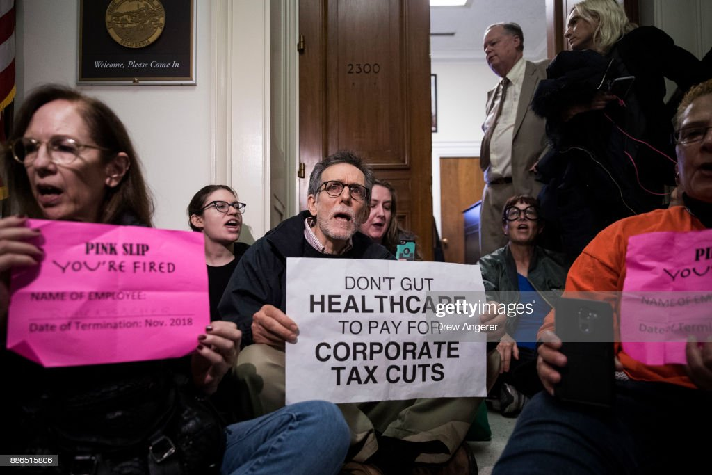 Activists stage a sit-in to protest the GOP tax reform bill, outside of office of Rep. Dana Rohrabacher (R-CA) on Capitol Hill, December 5, 2017 in Washington, DC. The next step in the legislative process for the GOP tax reform plan is to merge the Senate and House versions in a conference committee.