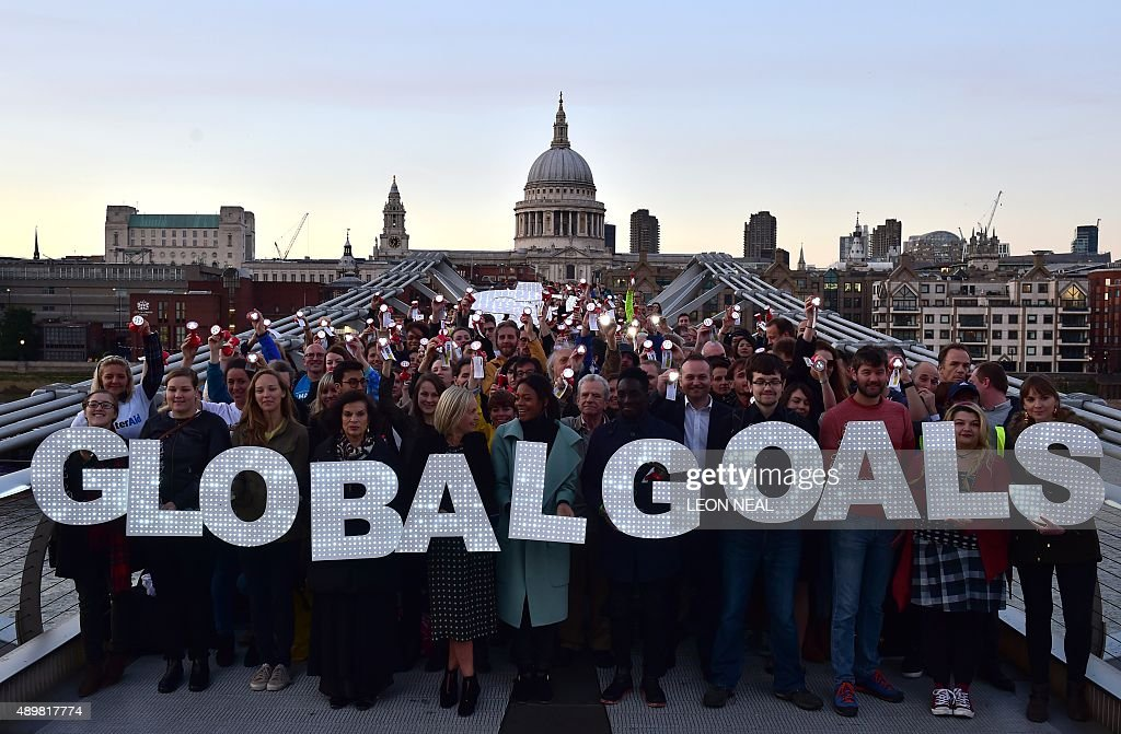 Activists stand on the Millennium bridge in London to demand action on poverty, inequality and climate change on September 24, 2015 on the eve of a United Nations summit tomorrow on sustainable developement. NEAL