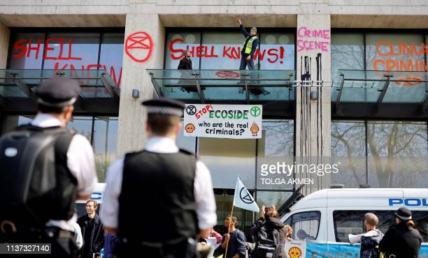 Activists stand on the porch covering the entrance to the Shell Centre, the UK offices of Royal Dutch Shell, as demonstrators surround the building...