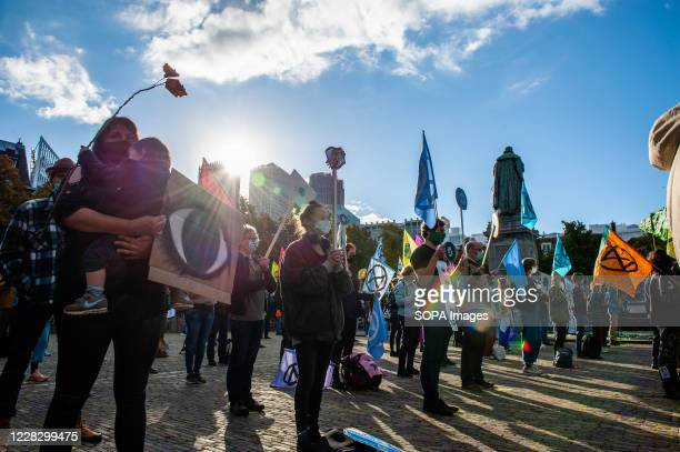 Activists standing at the House of Parliament while holding climate placards during the demonstration. The climate activist group, Extinction...