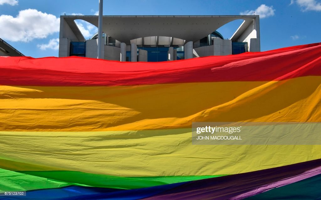 Activists stretch a giant rainbow banner in front of the Chancellery in Berlin on April 30, 2017, during a demonstration calling on Russian President to put an end to the persecution of gay men in Chechnya. The protestors called on German Chancellor Angela Merkel, who will meet Putin in Sochi on May 2, 2017, to raise the issue with him. / AFP PHOTO / John MACDOUGALL