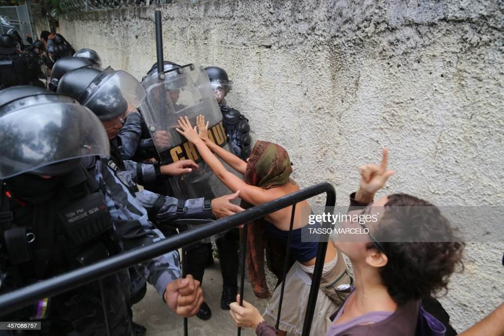 Activists struggle with riot police during a demonstration near the Museu do Indio (Indian Museum) 'Aldea Maracana' (Maracana Village) in Rio de Janeiro, Brazil, on December 16, 2013. The demonstrators, among whom there were some 30 Amazonic natives, seized the museum protesting against its scheduled demolition to continue the works in the Mario Filho 'Maracana' stadium ahead of the FIFA WC Brazil 2014.