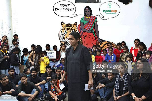Activists take part in a play in front of a mural depicting fictional character Priya who is a rape survivor sitting on a tiger before a march...