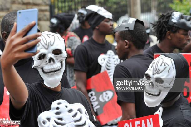 Activists take selfies while demonstrating on June 5 2018 in Nairobi where more than a hundred proteste on World Environment Day carrying placards...