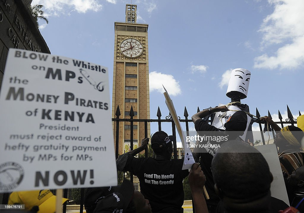 Activists tie a noose on an effigy symbolising Kenyan MPs on a gate, on January 14, 2013 in front of the parliament in Nairobi, during a demonstration against the lawmakers had voted for themselves a $107,000 sendoff bonus after their first attempt was vetoed by the President. The proposed pay off -- at a cost to the country of $23.7 million -- came after Kenya's parliament dismissed the majority of wage demands of striking public sector workers, including nurses who are currently on strike over pay demands. Kenyan lawmakers are already some of the best paid on the continent, with a tax-free monthly salary of some $13,000.AFP PHOTO/Tony KARUMBA