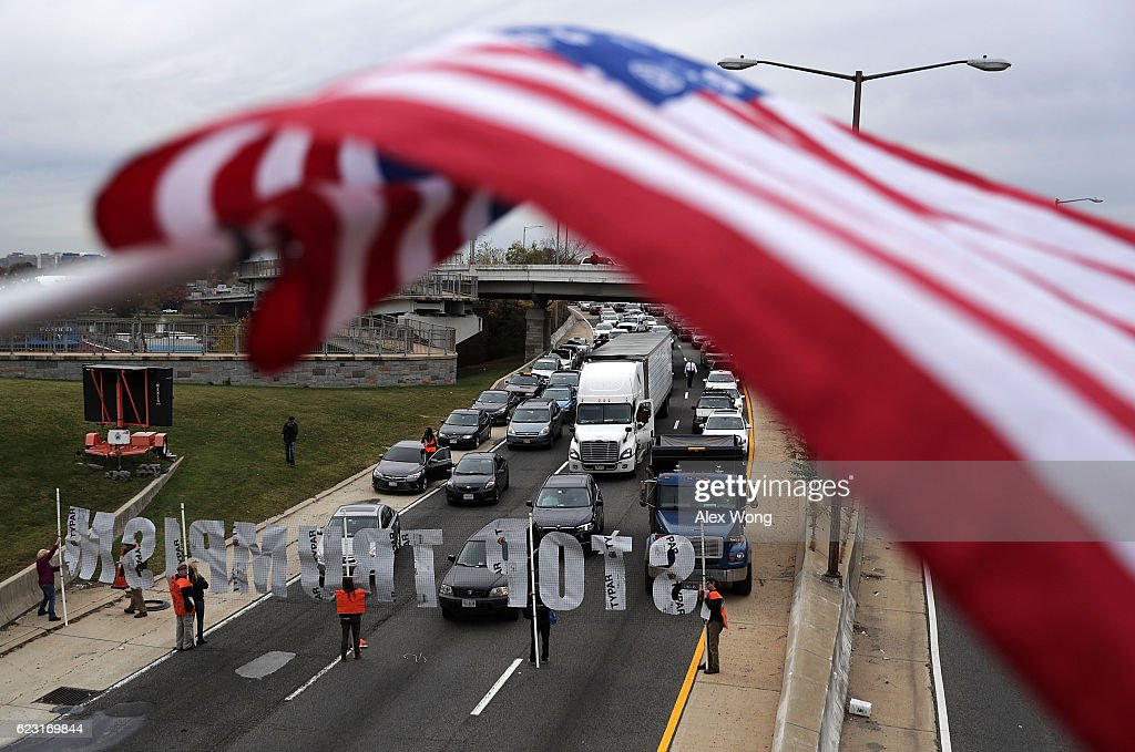 Activists use a banner to block traffic on I-395 during an anti-Trump and anti-TPP protest November 14, 2016 in Washington, DC. Activists held a rally and a march 'to protest the Trans-Pacific Partnership and urge President-elect Donald Trump and members of Congress to reject the trade deal.'