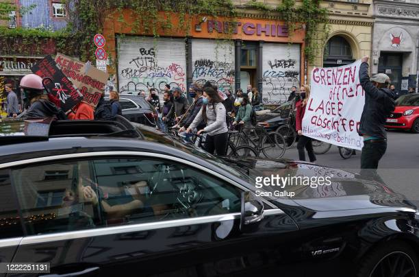 Activists walk past men in a Mercedes during scattered leftwing protests in Kreuzberg district on May Day during the novel coronavirus crisis on May...
