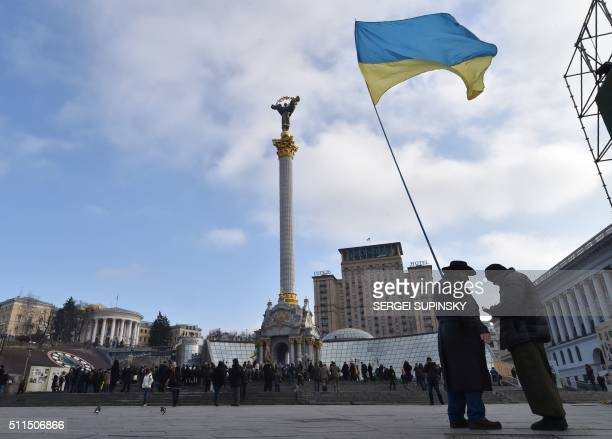 TOPSHOT Activists wave a Ukrainian flag on Independence Square in Kiev on February 21 2016 Protesters of the Radical Right Power organization pitched...