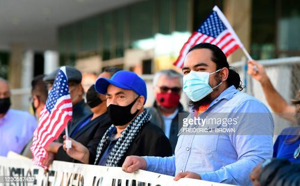 Activists wave US flags during a rally outside the Federal Building in Los Angeles, California on January 14, 2021. - Los Angeles Immigrant Groups...