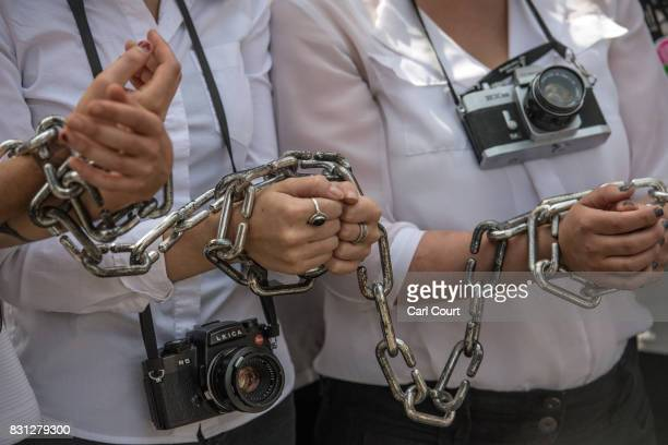 Activists wear chains on their wrists as they protest outside the Egyptian Embassy to highlight the plight of jailed Egyptian photojournalist...