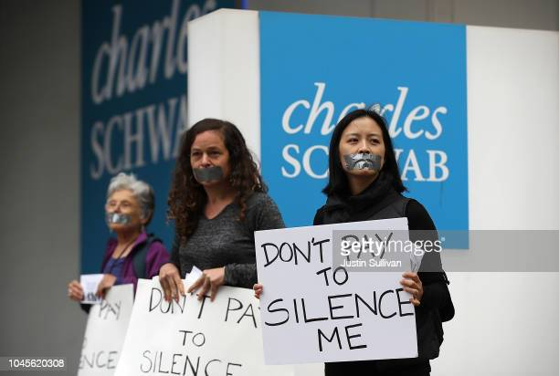 Activists wear tape on their mouths and hold signs as they protest in front of the Charles Schwab headquarters on October 4 2018 in San Francisco...