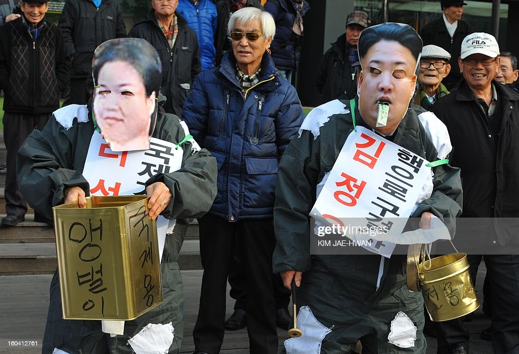 activists wear the face masks of North Korean leader Kim Jong-Un and his wife Ri Sol-Ju (L) as they 'beg' for money during an anti-Pyongyang rally urging North Korea to abandon nuclear weapons in Seoul on January 31. South Korean President Lee Myung-Bak held an emergency security meeting on January 31 that warned North Korea of 'serious consequences' if it went through with an expected nuclear test.