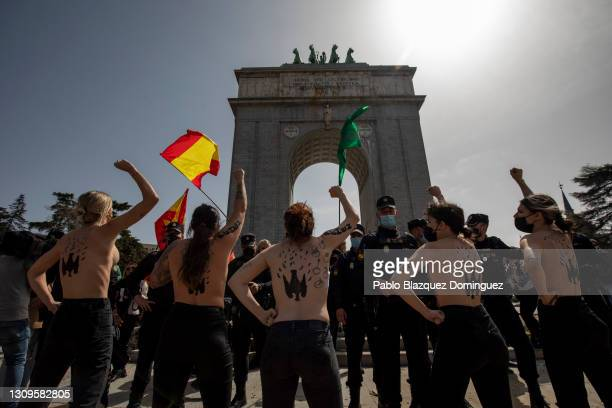Activists wearing body paint raise their fists during a gathering of right-wing supporters at Arco de la Victoria commemorating the 82nd anniversary...