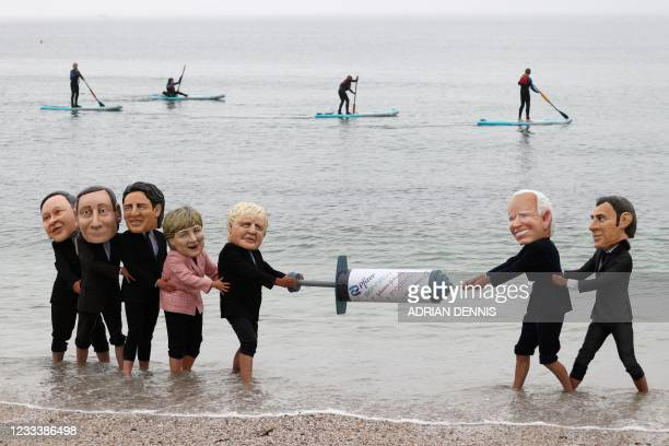 Activists wearing giant heads of the G7 leaders tussle over a COVID-19 vaccine syringe during an action by charity Oxfam to highlight intellectual...