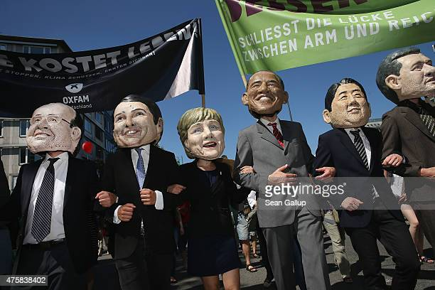 Activists wearing masks that look like the leaders of the G7 group of nations join a protest march against the upcoming G7 summit and attended by...