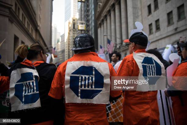 Activists wearing orange prison jumpsuits with the Chase Bank logo rally against financial institutions' support of private prisons and immigrant...