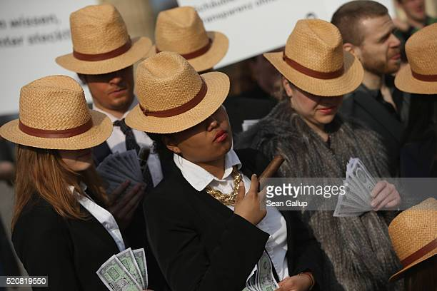 Activists wearing suits and Panama hats hold fake money while demanding greater trasparency in new legislation following the ongoing Panama Papers...
